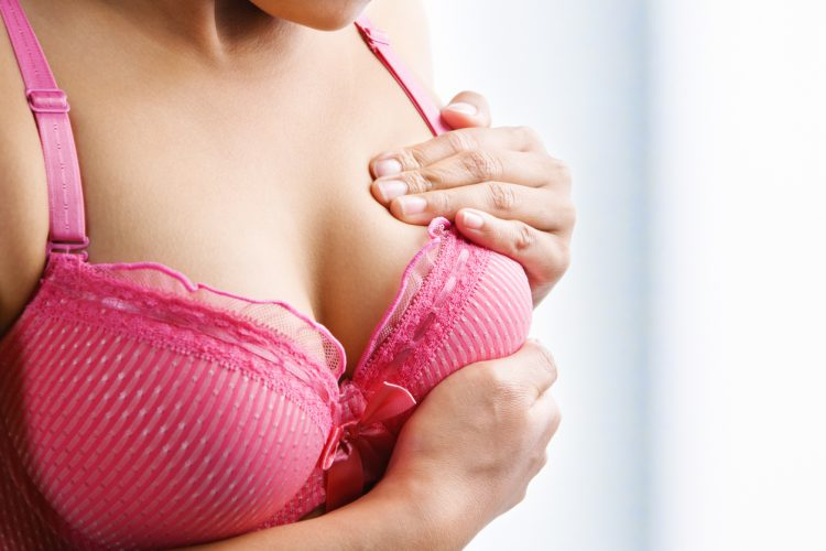 Woman Checking Breast for Lumps