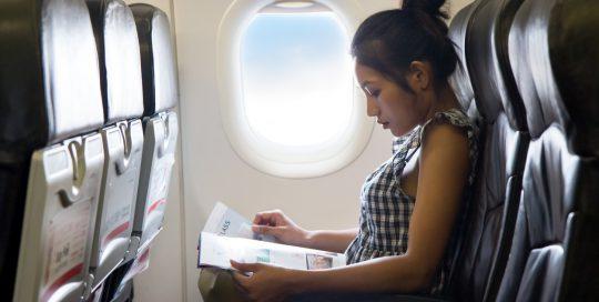 Woman Reading Magazine on Airplane