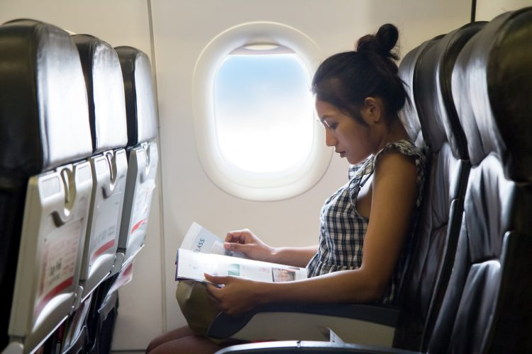 Woman Reading Magazine on Airplane