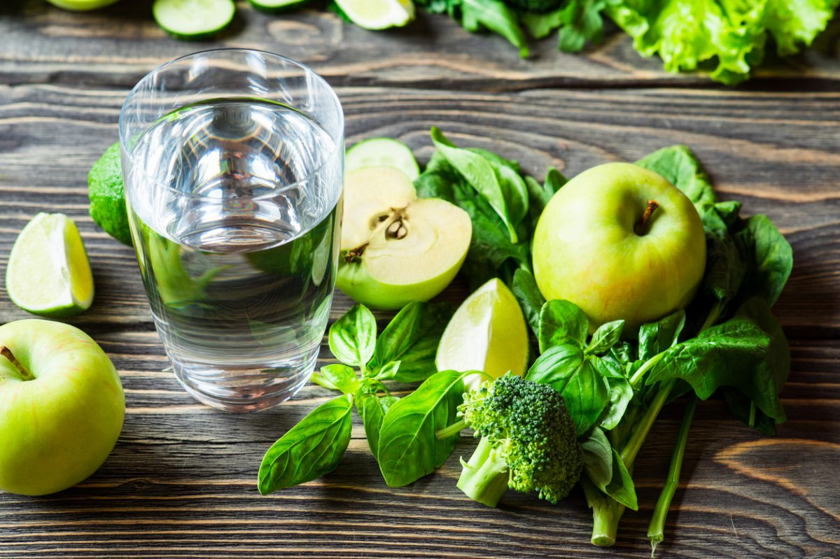 Glass of Water Next to Green Fruits and Vegetables