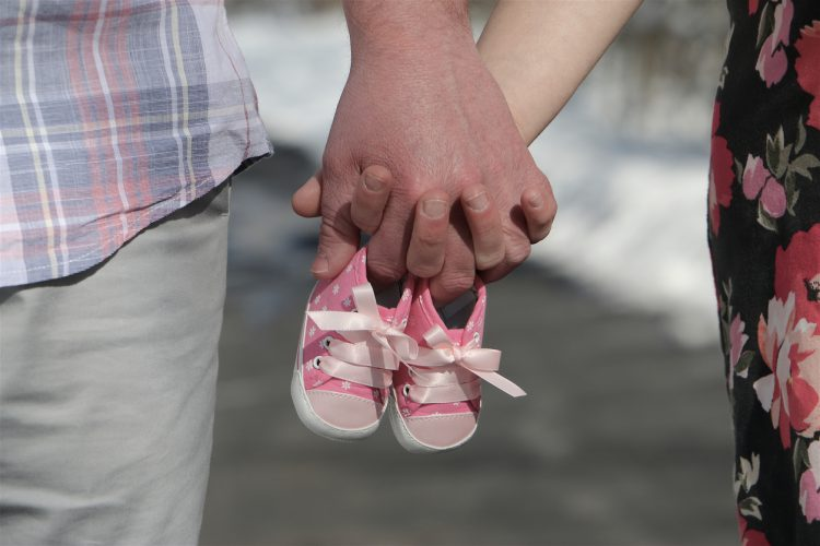 Man and Woman Holding Baby Shoes