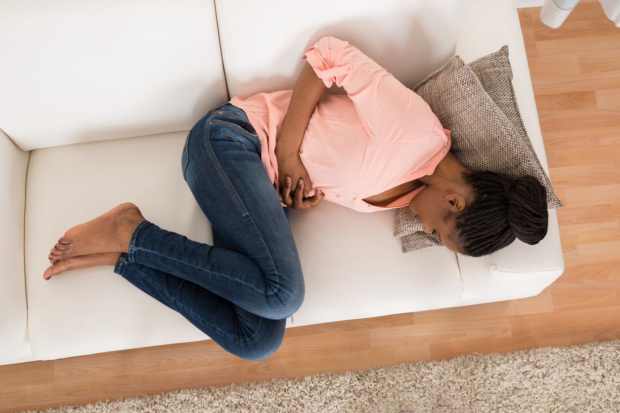Woman Lying on Couch Holding Stomach
