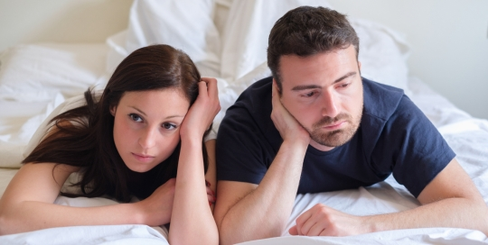 Couple Laying on Stomach in Bed