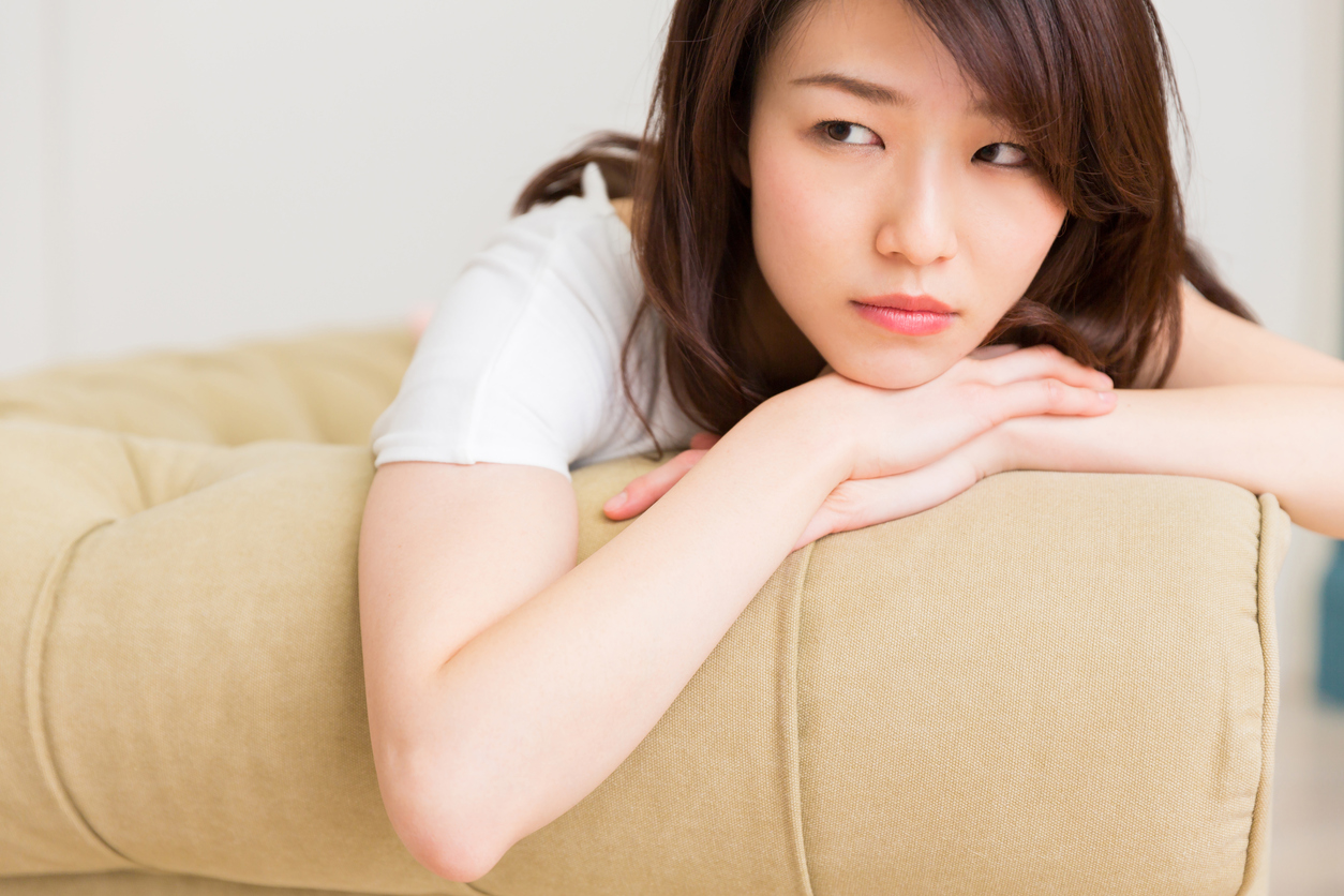 Woman Sitting on Couch in Thought