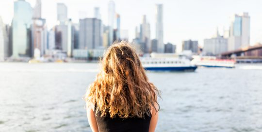 Back of young woman outside outdoors in NYC New York City Brooklyn Bridge Park by east river, railing, looking at view of cityscape skyline